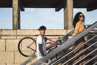Young couple climbing stairs, carrying bicycle - RCPF00062