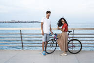 Young couple with bicycle, standing on bridge by the sea - RCPF00065
