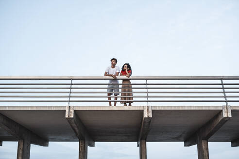 Young couple standing on bridge, looking at view - RCPF00071