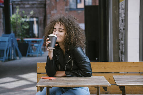 Portrait of happy teenage girl enjoying coffee to go at pavement cafe - VPIF01542