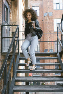 Portrait of smiling teenage girl with coffee to go walking downstairs - VPIF01545