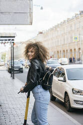 Portrait of smiling teenage girl with scooter standing on pavement - VPIF01560