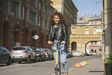 Portrait of smiling teenage girl riding scooter on pavement - VPIF01563