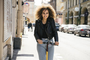 Portrait of smiling teenage girl riding scooter on pavement - VPIF01569