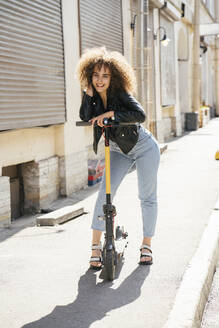 Portrait of happy teenage girl standing with scooter on pavement - VPIF01572