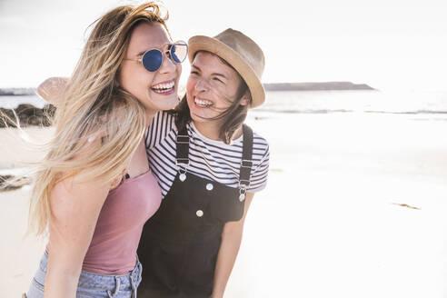 Two girlfriends having fun, walking on the beach - UUF19016