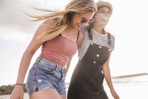 Two girlfriends having fun, walking on the beach - UUF19022
