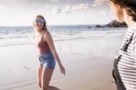 Two girlfriends having fun, walking on the beach - UUF19028