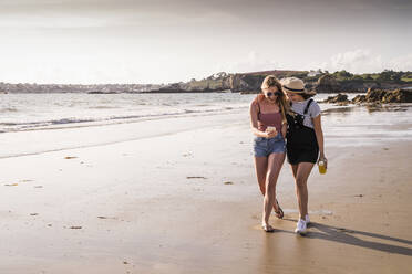 Two girlfriends having fun, walking on the beach, taking smartphone selfies - UUF19034