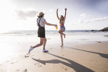 Two girlfriends having fun, running and jumping on the beach - UUF19037