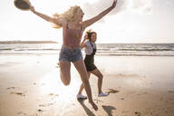 Two girlfriends having fun, running and jumping on the beach - UUF19040