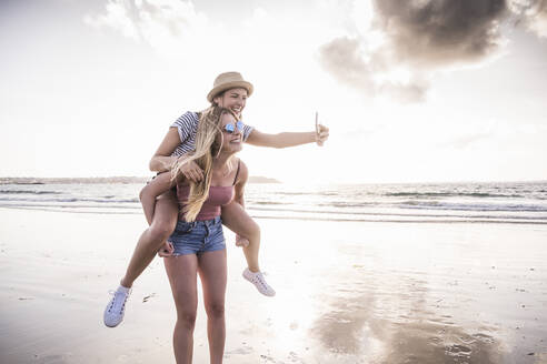 Two girlfriends having fun on the beach, carrying each other piggyback, taking smartphone selfies - UUF19046