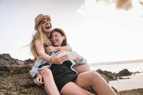 Two girlfriends sitting on rocky beach, taking smartphone selfies - UUF19049
