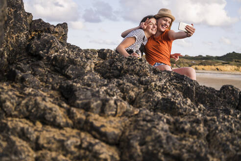 Two girlfriends sitting on rocky beach, taking smartphone selfies - UUF19055