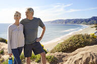 Smiling senior couple standing on cliff at beach against sky during sunny day - CAVF64940