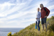 Smiling senior couple standing on cliff by sea against sky - CAVF64946