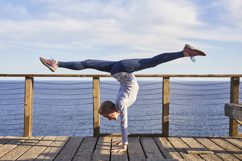 Full length senior woman doing handstand while exercising on floorboard by sea against sky - CAVF64949