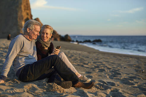 Senior couple using phone while sitting on sand at beach during sunset - CAVF64964