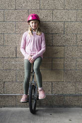 Young Girl Balancing on Unicycle Against Brick Wall - CAVF65045