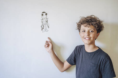 Portrait of smiling boy pointing to a drawing on a whiteboard - DLTSF00212