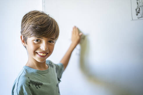 Portrait of happy boy in front of drawing on a whiteboard - DLTSF00218