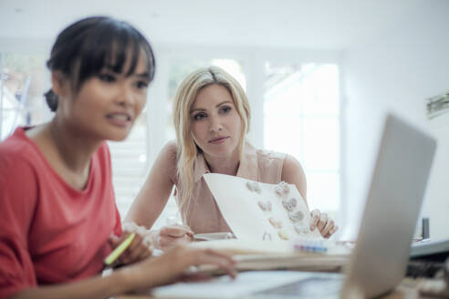 Two women with laptop working on fashion designs on table - AJOF00025