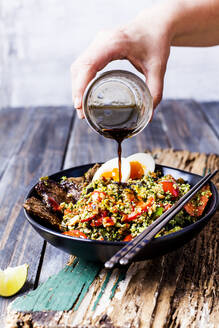Pouring sauce over Thai style fried broccoli rice(shreddedbroccoli)with beef slices, eggs, and spicy sauce(ketogenicdiet, paleodiet, lowcarb) - SBDF04025