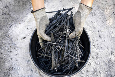 Hands holding self made charcoal outdoors - NDF00985
