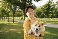Smiling boy holding his Welsh Corgi Pembroke in a park - VPIF01589