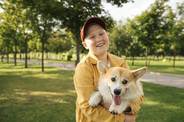 Smiling boy holding his Welsh Corgi Pembroke in a park - VPIF01589