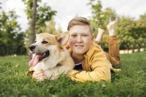 Boy with Welsh Corgi Pembroke in a park - VPIF01595