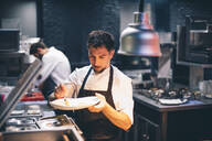 Chef serving food on a plate in the kitchen of a restaurant - CJMF00089