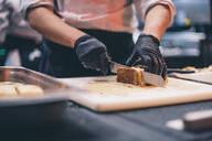 Chef at work cutting a cake in a restaurant kitchen - CJMF00095