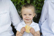 Portrait of little girl with a snack sitting amidst parents - MGIF00765