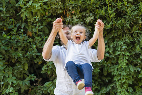 Happy father playing with little daughter in a park - MGIF00771