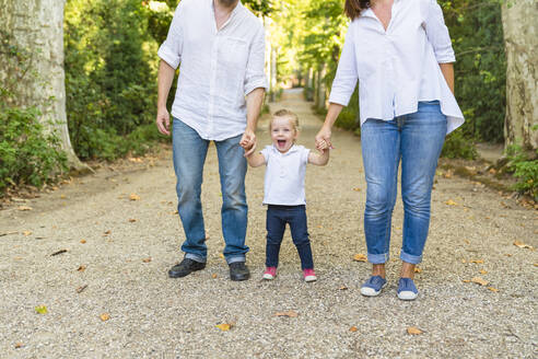 Happy girl walking hand in hand with parents in a park - MGIF00774