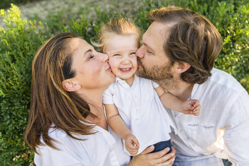 Parents kissing happy little daughter - MGIF00777