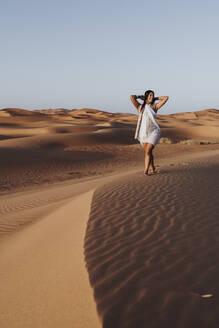 Beautiful young woman walking in the desert, Merzouga, Morocco - DAMF00124