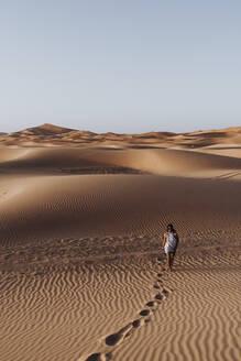 Young woman walking in the desert, Merzouga, Morocco - DAMF00127