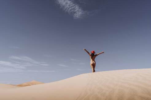Nude young woman wearing a hat in the desert, Merzouga, Morocco - DAMF00130