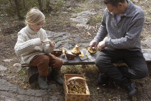 Father and daughter cleaning mushrooms on bench - JOHF02124