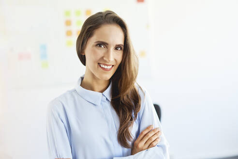 Young businesswoman standing in office smiling at camera - BSZF01466
