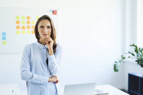 Portrait of confident young businessowman standing in office looking at camera - BSZF01469