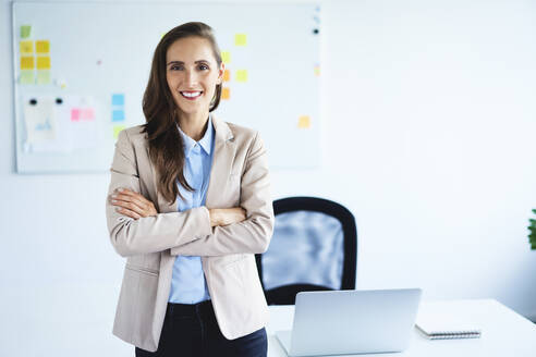 Cheerful young businesswoman looking at camera with crossed arms standing in office - BSZF01475
