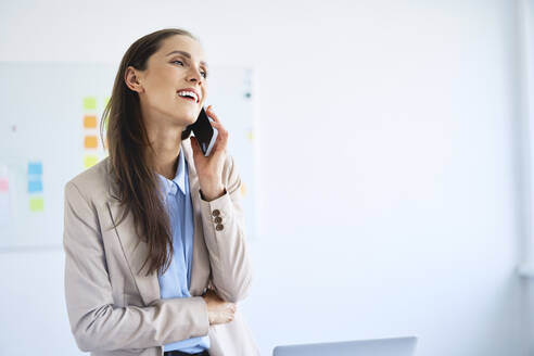 Cheerful businesswoman talking on phone in office - BSZF01478