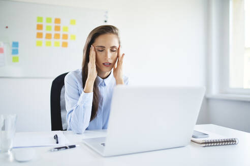 Young businesswoman sitting in office suffering from headache - BSZF01499
