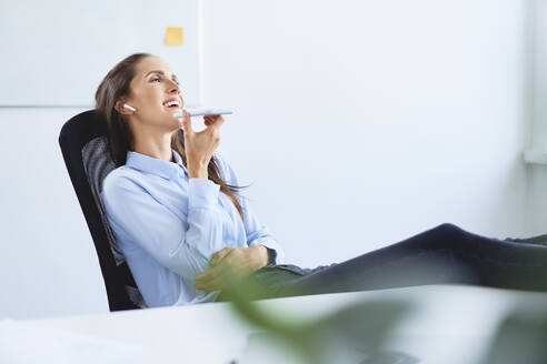 Cheerful businesswoman reclining in chair talking on phone - BSZF01502