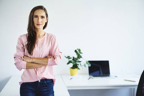 Portrait of confident young businesswoman leaning against desk in office - BSZF01511