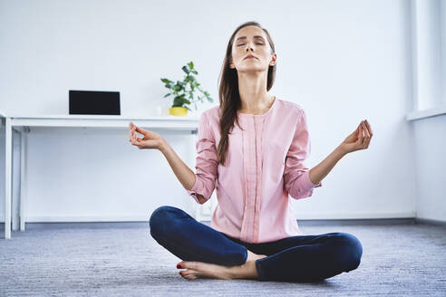 Young woman meditating on floor in office - BSZF01517