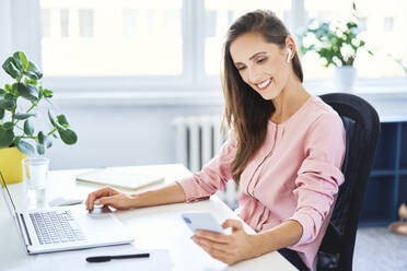 Young businesswoman checking phone while working on laptop in office - BSZF01523